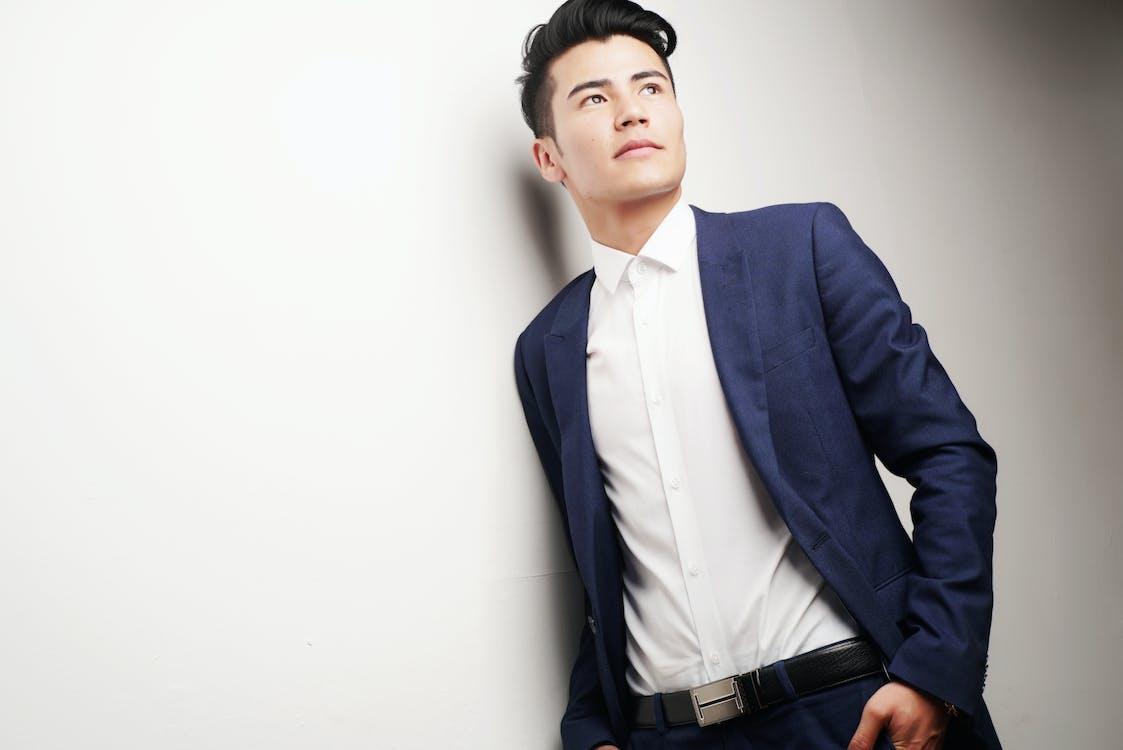 Man Wearing Blue Blazer and White Dress Shirt Leaning on White Wall