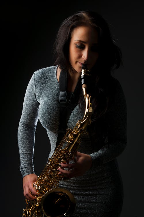 Woman in Gray Long Sleeve Shirt Playing Saxophone