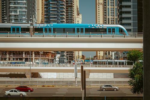 Modern train driving on bridge above road in city