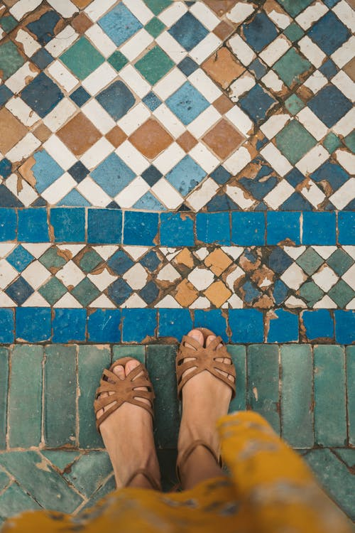 Person in Sandals Standing on Blue and White Floor Tiles