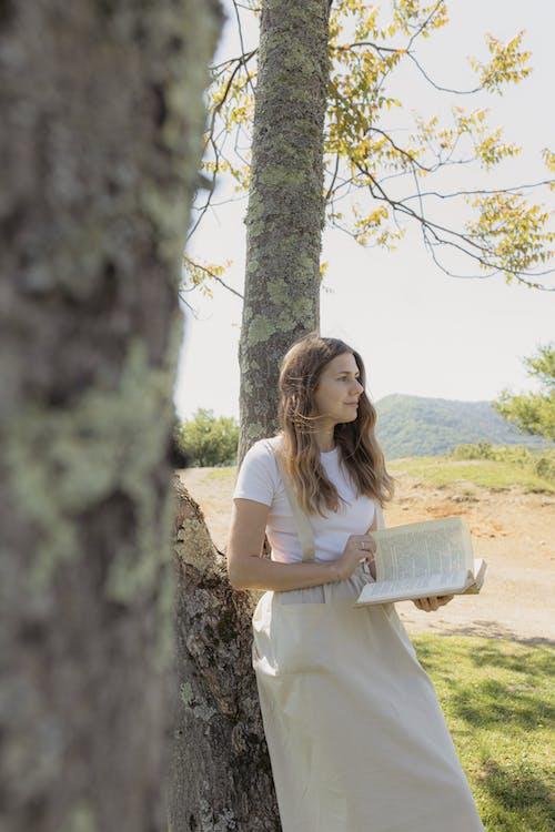 Woman in White Dress Standing Beside Tree