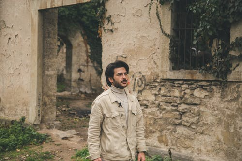 Trendy bearded ethnic male with hairstyle near aged house with weathered walls on street looking away