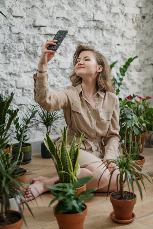 Woman in Brown Button Up Long Sleeve Shirt Taking Selfie Using Smartphone