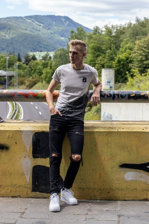 Man in White Crew Neck T-shirt and Black Pants Leaning on Railing