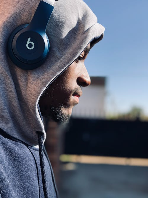 Side view of crop pondering masculine African American male listening to music in wireless headphones in town while looking down