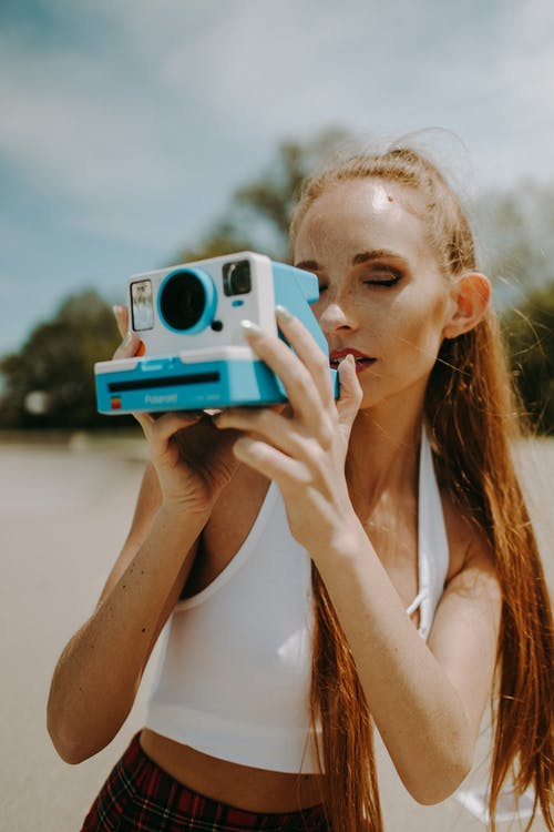 Woman in White Tank Top Holding Teal and White Camera