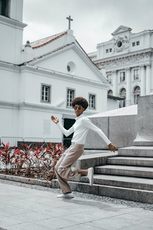 Man in White Dress Shirt and Brown Pants Jumping on Gray Concrete Stairs