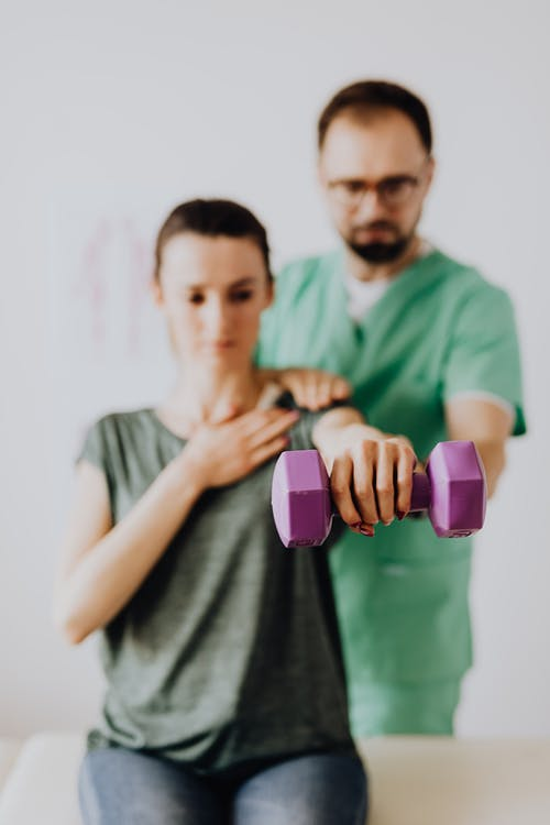 Chiropractor assisting female patient with dumbbell in doctor office