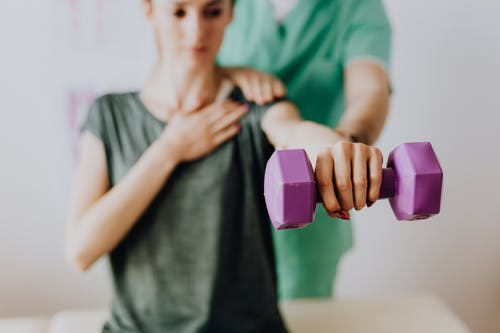 Crop anonymous osteopath assisting patient with dumbbell in hand