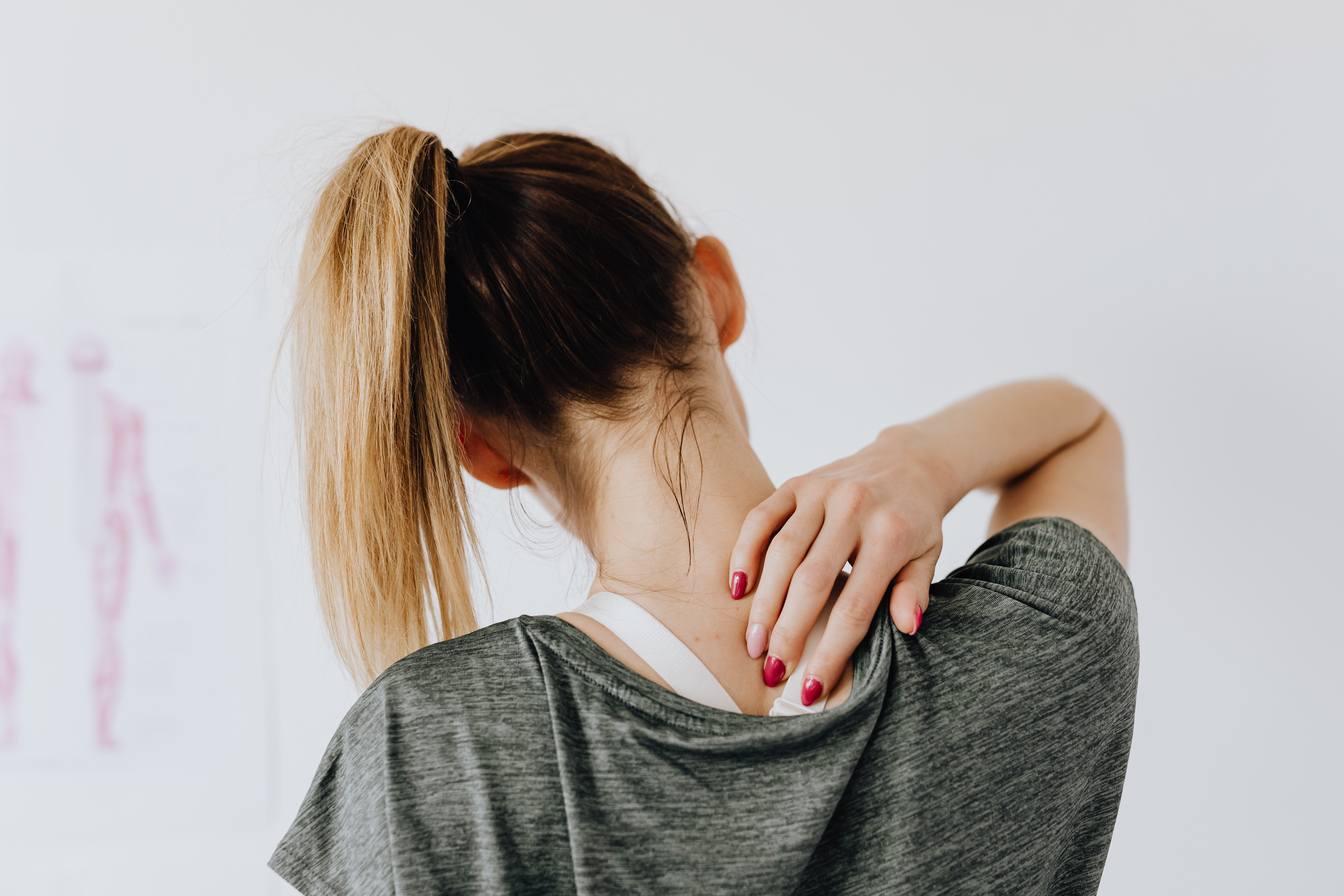 woman touching her aching upper back