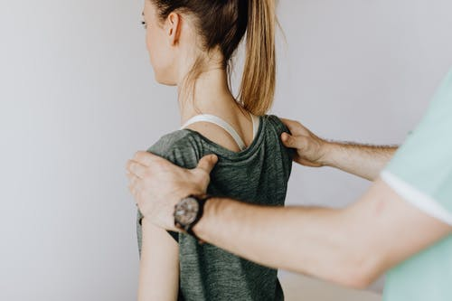 Back view of crop faceless orthopedist in uniform and wristwatch examining shoulder joints of slim female patient in clinic on white background