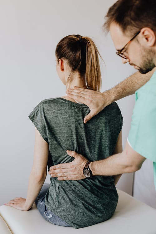 Crop osteopath examining back of anonymous woman in doctor office