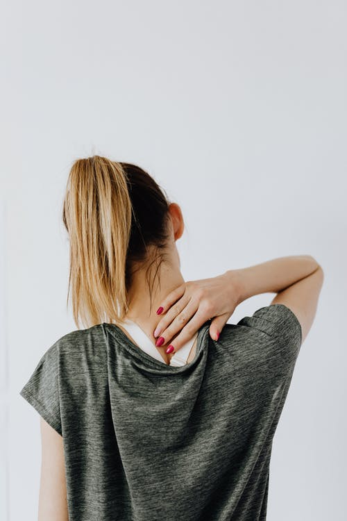 Anonymous female with spinal pain on white background