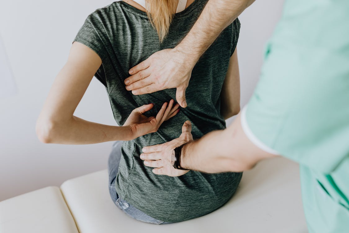 Crop unrecognizable woman showing chiropractor painful spot on back