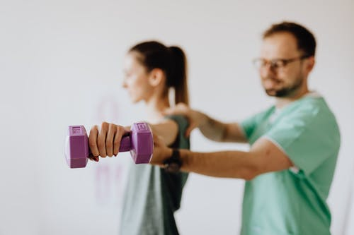 Chiropractor examining female patient with reached arm and dumbbell