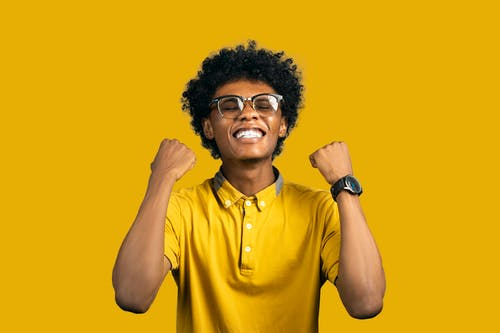 Excited African American man with accessories showing yes gesture
