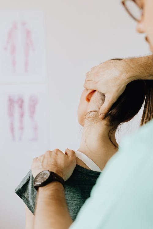 Crop chiropractor examining neck of female patient in clinic