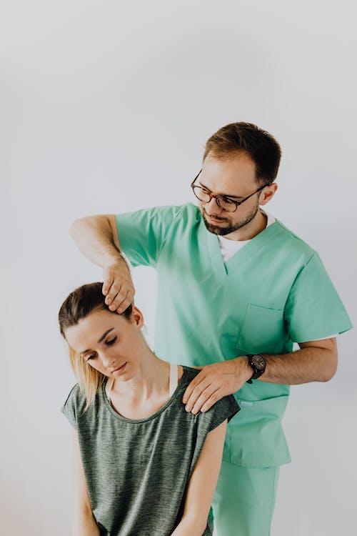 Chiropractor in uniform examining neck of female patient in clinic