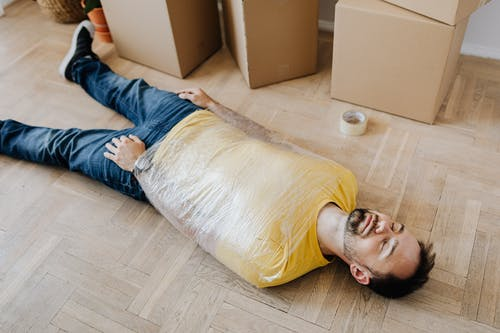 High angle of tired male in casual wear wrapped in plastic tape and lying on parquet with eyes closed near carton boxes during relocation