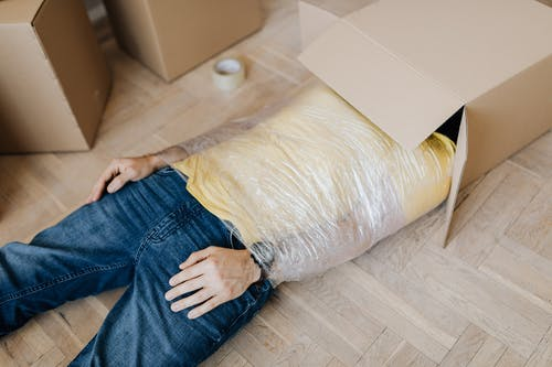 Man tied up using tape with head in carton box
