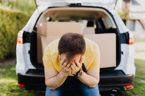 Faceless frustrated tired male wearing casual outfit sitting on car luggage boot and covering face with hands during relocation on sunny summer day