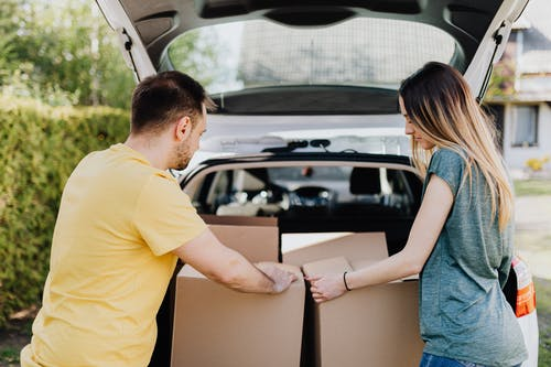 Calm couple putting carton boxes into car trunk