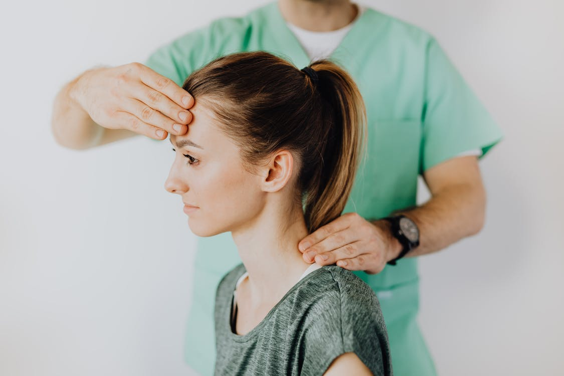 Professional massage therapist performing head and neck massage on content female patient relieving sore neck tensions