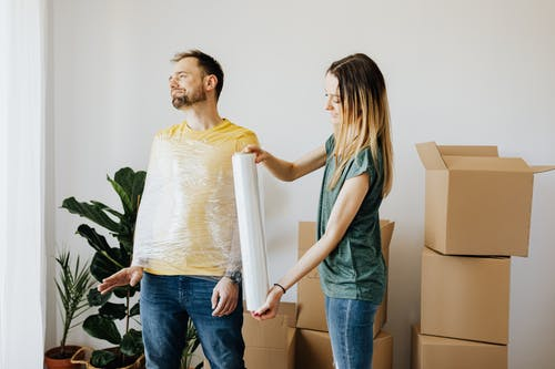 Content couple having fun while girlfriend in casual wear wrapping boyfriend with clingy plastic roll during packing belongings into carton boxes before moving in together