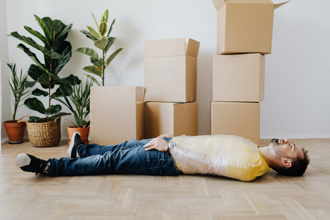 Full body side view unemotional male wearing casual outfit lying on floor with upper body tied up with tape and tired after packing belongings into carton boxes
