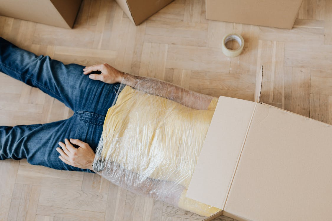 From above anonymous male in casual clothing lying on parquet with box on head and upper body wrapped in clingy plastic tape during moving out