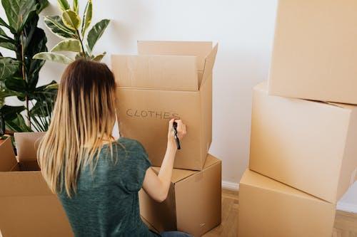 Woman writing on carton box word clothes