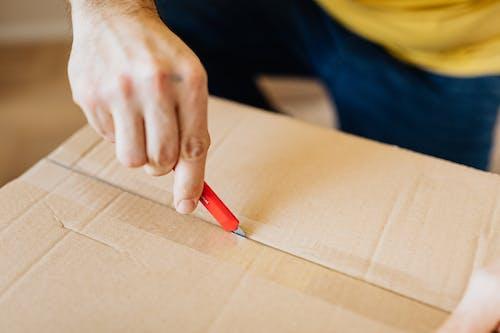 Crop man unsealing carton box with cutter knife