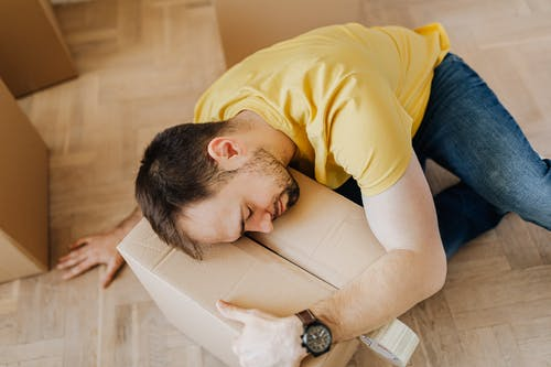 High angle of fatigued male in casual wear sleeping on floor with cardboard box after packing belongings before moving out