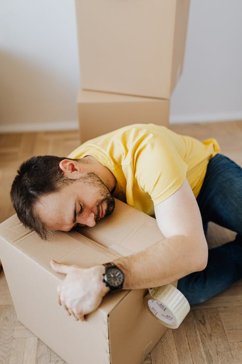 Fatigued young man lying asleep on floor with carton box
