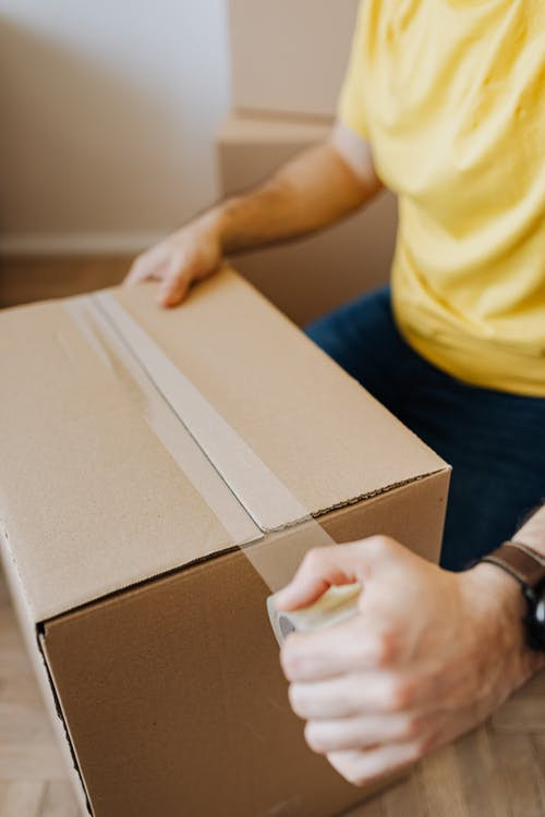 Crop anonymous guy in casual clothes using clingy tape to seal cardboard box for courier during relocation