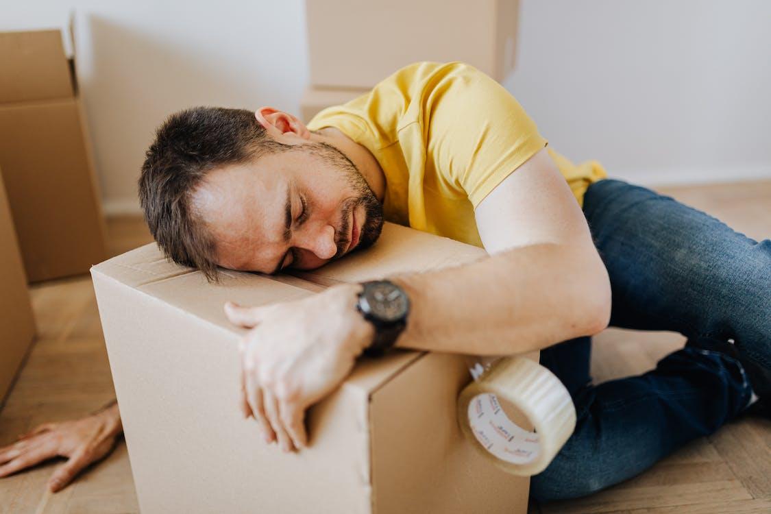 Tired man fell asleep on carton box