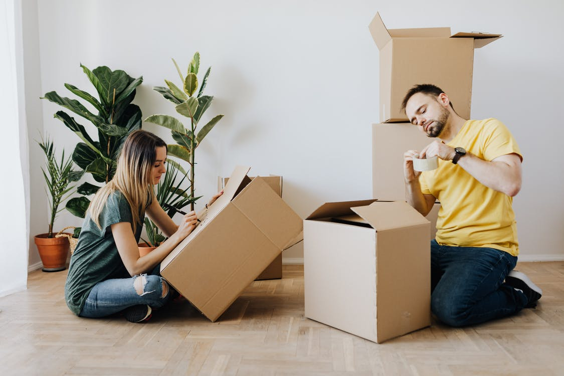 Content couple packing belongings into carton boxes