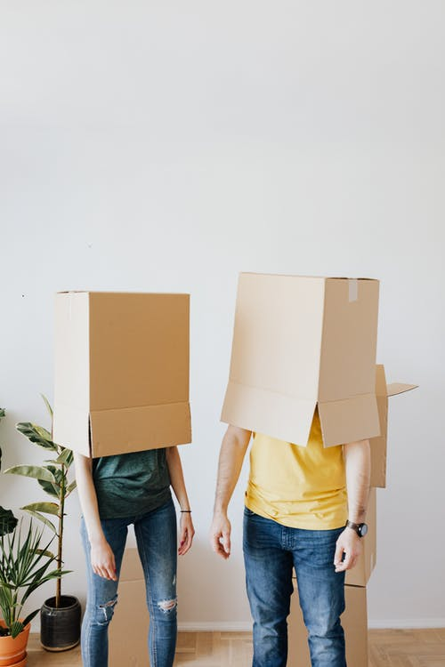 Unrecognizable couple carrying carton boxes on heads