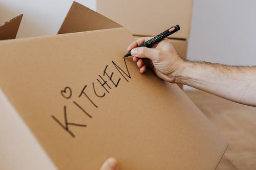 Crop unrecognizable male using marker to write on carton box word kitchen and draw cute heart while packing kitchenware before relocation