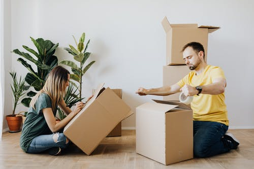 Side view full body unemotional couple wearing casual clothes and sitting on parquet while sealing carton boxes with tape and writing notes during moving in together