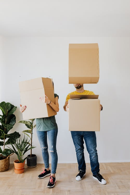 Full body anonymous couple in casual clothes carrying and playing with carton boxes in excitement during relocation into new flat