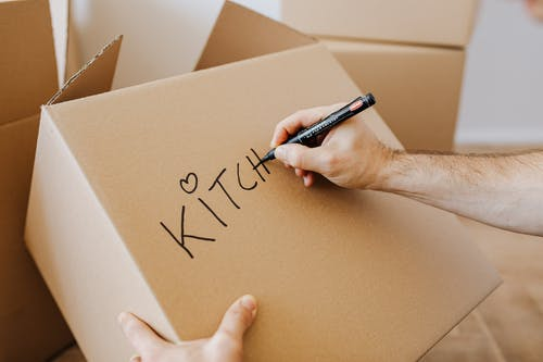 From above of unrecognizable adult male writing with black marker on cardboard containers while packing staff and preparing for relocation in new home