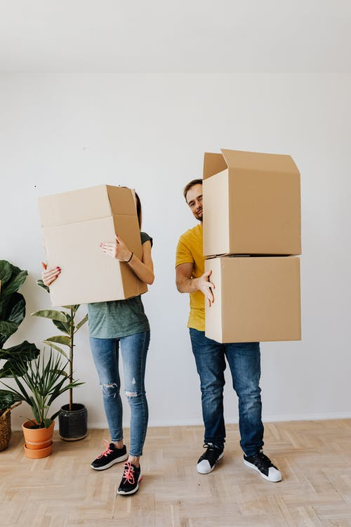 Adult woman and man wearing casual clothes standing near potted plants with cardboard containers while moving to new house together