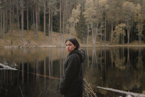 Woman in Black Coat Standing Near Lake