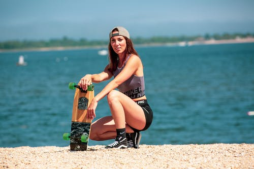 Side view of young slim sportswoman in active wear squatting on shabby shore with skateboard near rippled lake while looking at camera