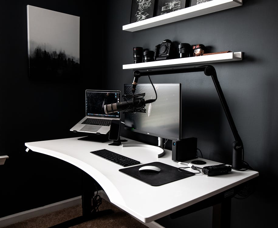 Contemporary style workspace with netbook near computer and microphone on white table in room with dark walls