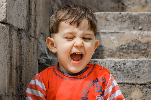 Little child shouting near shabby walls on street