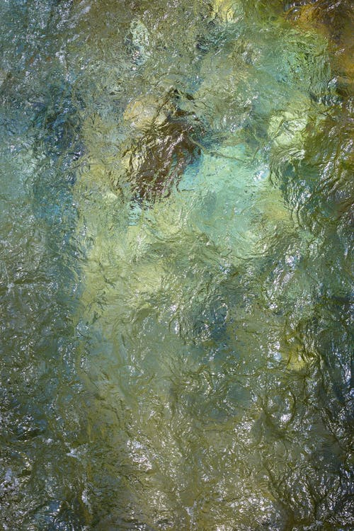 Top view of reflective water of clear calm river rippling and flowing in nature