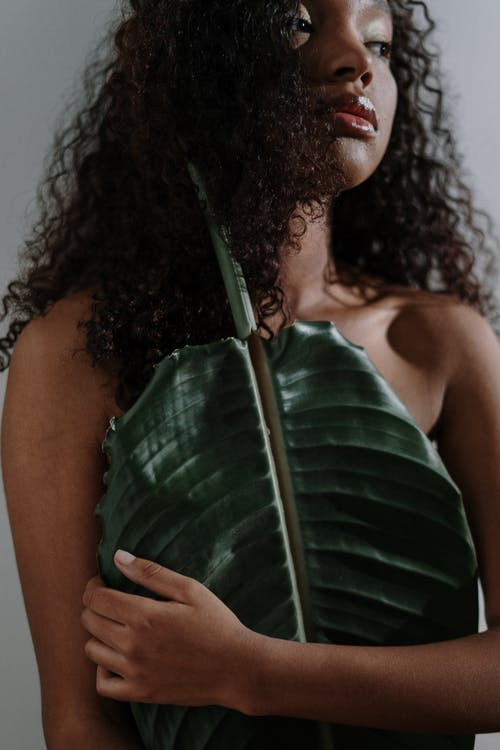 Woman in Green Tank Top Holding Green Leaf