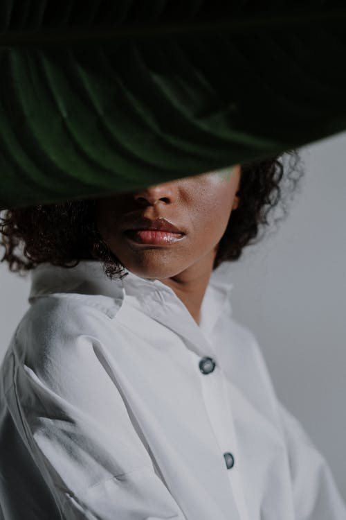 Woman in White Button Up Shirt Wearing Green and Black Hat